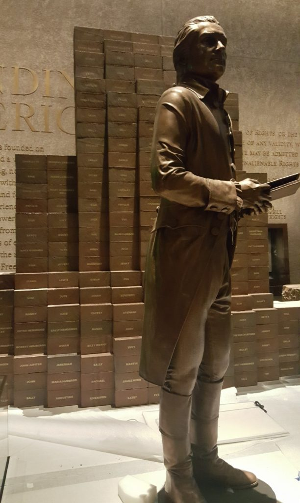 Thomas Jefferson stands in front of a wall dedicated to the Declaration of Independence while each brick behind him represents his slaves.